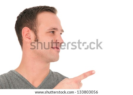 Smiling young man looking sideways towards centre frame and pointing with his finger to blank copy space isolated on white - stock photo