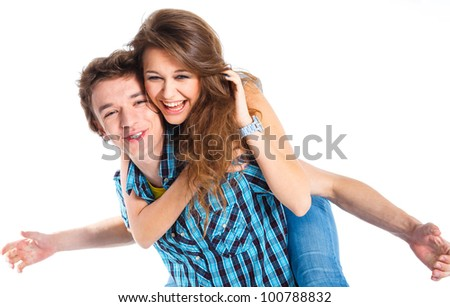 Smiling young man piggybacking his pretty girlfriend. Isolated on white background. - stock photo