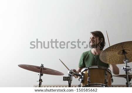 Smiling young man playing drum set - stock photo