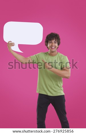 Smiling young man pointing at speech bubble over pink background - stock photo