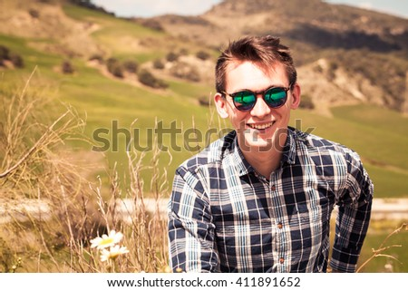 Smiling young man posing outdoors in the countryside. - stock photo