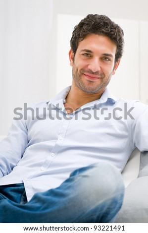 Smiling young man relaxing and sitting on sofa at home - stock photo