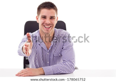 Smiling young man shaking hands across the table  - stock photo