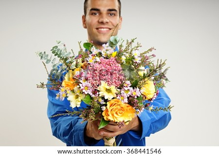 Smiling young man shows bouquet of flowers, focus is on flower - stock photo