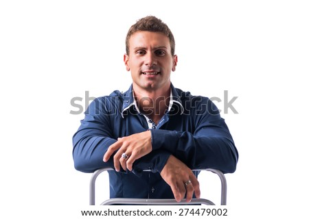 Smiling young man sitting on chair backwards, isolated on white - stock photo