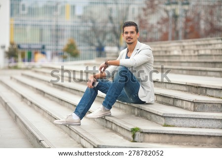 Smiling young man sitting on the stairs holding mobile phone - stock photo