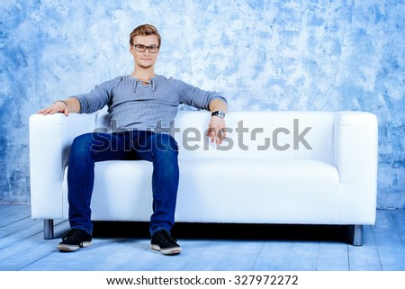 Smiling young man sitting relaxed on a sofa.  - stock photo