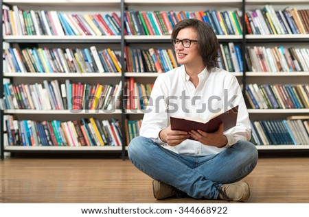 smiling young man sitting with crossed legs on the floor in the library with an open book in his hands, looking to the right, blurred book shelves at the background, a concept of reading