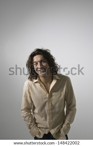 Smiling young man standing against gray background - stock photo