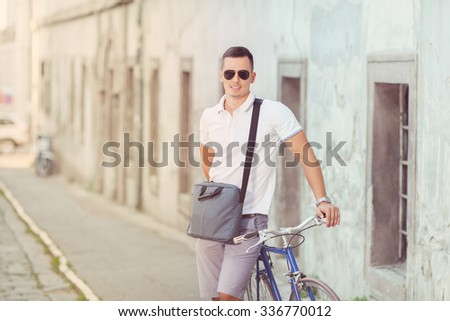 Smiling young man standing on the street with his bicycle beside him - stock photo