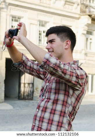 Smiling young man standing outdoors in an urban environment taking a photograph - stock photo