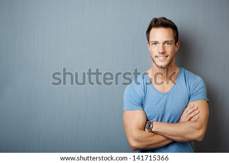 Smiling young man standing with arms crossed against gray background - stock photo