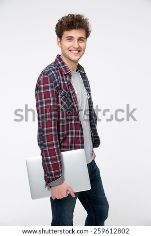 Smiling young man standing with laptop over gray background - stock photo