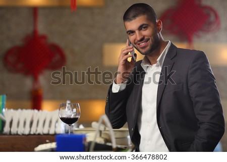Smiling young man talking on the phone while drinking wine at the bar - stock photo