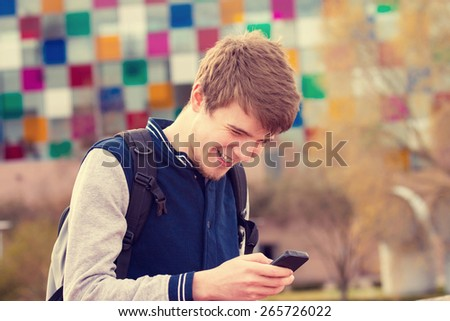 Smiling young man taping on mobile phone in a city .Young smiling student  outdoors talking on cell smart phone.Life style.City - stock photo