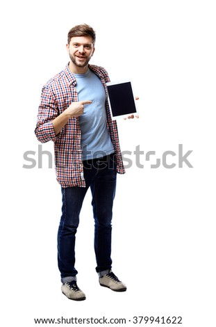 Smiling young man using tablet computer against a white background - stock photo