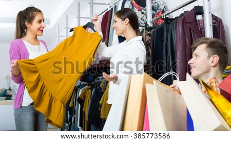 Smiling young man waiting for his girlfriend choosing apparel