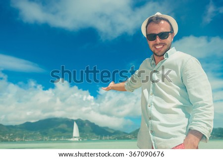 smiling young man wearing sunglasses presenting from the beach a boat on the exotic sea