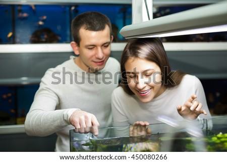 Smiling young man with happy girlfriend choosing aquarium fish in aquarium - stock photo