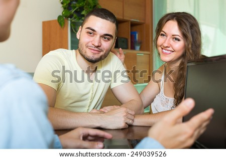 Smiling young married couple talking with employee with laptop at home  - stock photo