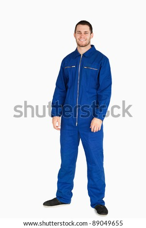 Smiling young mechanic in boiler suit against a white background - stock photo