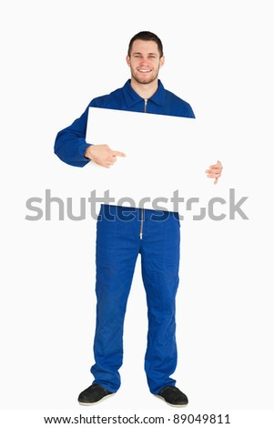 Smiling young mechanic in boiler suit pointing on banner in his hands against a white background - stock photo