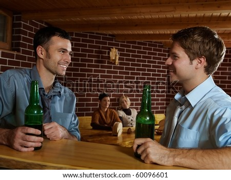 Smiling young men sitting at bar in pub drinking beer, women sitting in background.? - stock photo