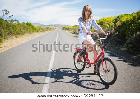 Smiling young model posing while riding bike down a deserted road in summertime - stock photo