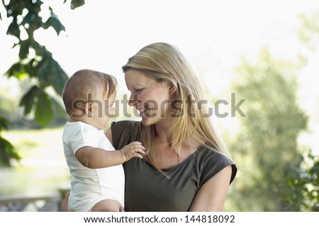 Smiling young mother and baby against blurred background
