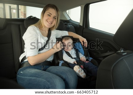 Smiling young mother and baby boy in car safety seat