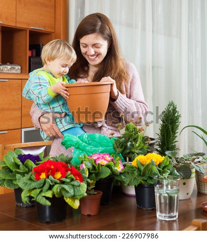 Smiling young mother and child with flowering plants in pots at home