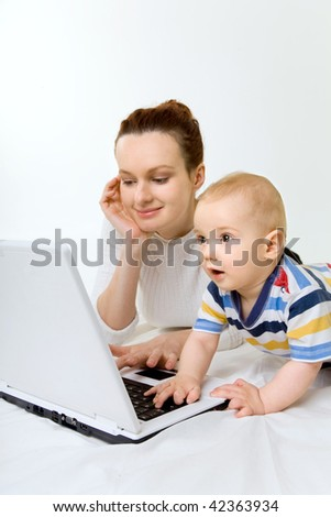 smiling young mother with baby playing with laptop