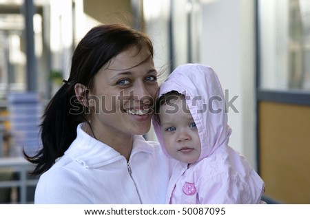 smiling young mother with charming daughter on hands