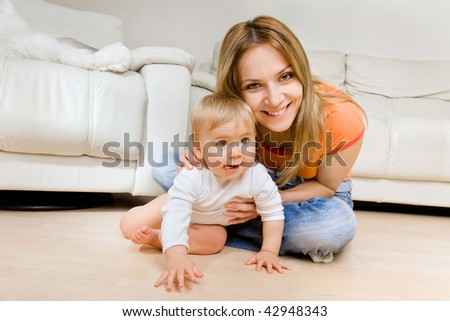 smiling young mother  with her baby - stock photo