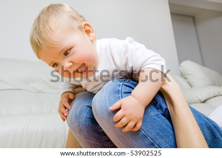 smiling young mother  with her baby having fun on her knees - stock photo