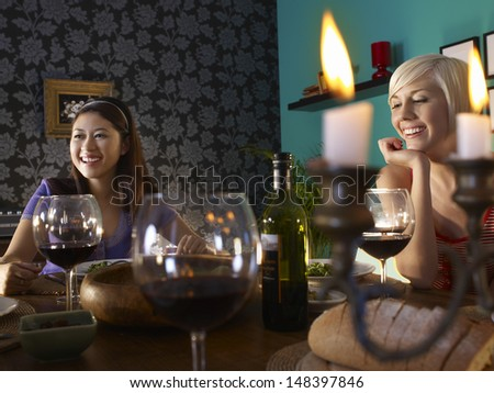 Smiling young multiethnic women enjoying dinner party - stock photo