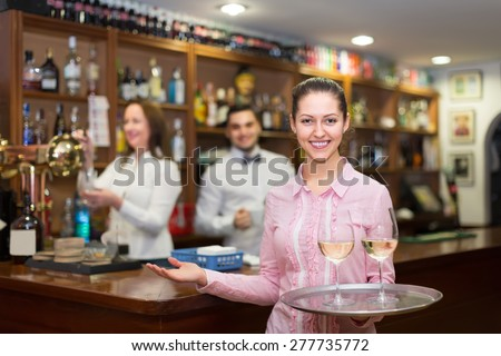 Smiling young nippy with beverages and bar crew at background - stock photo