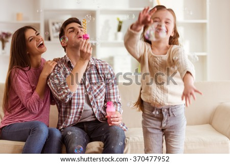 Smiling young parents and their child are very happy, they are at home - stock photo