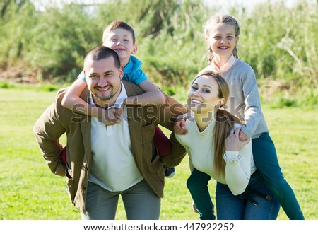 Smiling young parents holding two kids on the shoulders outdoors. Focus on boy - stock photo