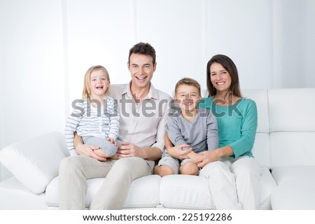smiling young parents on white sofa - stock photo