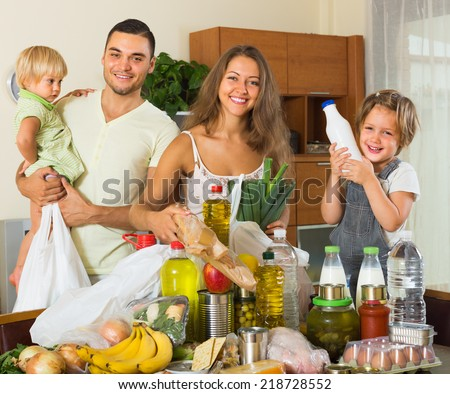 Smiling young parents with two little kids came back from supermarket  - stock photo