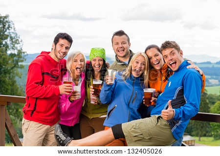 Smiling young people posing with beer and landscape background - stock photo