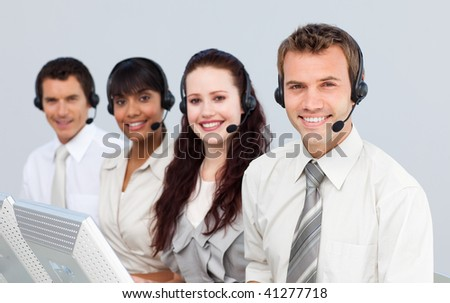 Smiling young people with a headset on working in a call center - stock photo