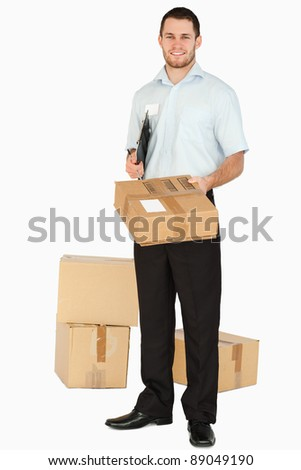Smiling young post employee with clipboard handing over parcel against a white background
