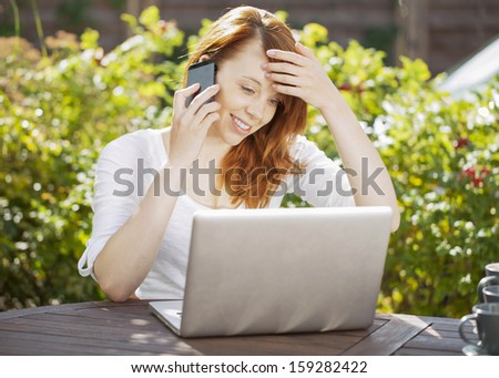 Smiling young redhead woman sitting at a wooden table in the garden in front of her laptop computer chatting on her mobile phone in the summer sunshine in front of green leaves - stock photo