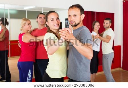 Smiling young romantic couple enjoying of partner dance in dance class - stock photo
