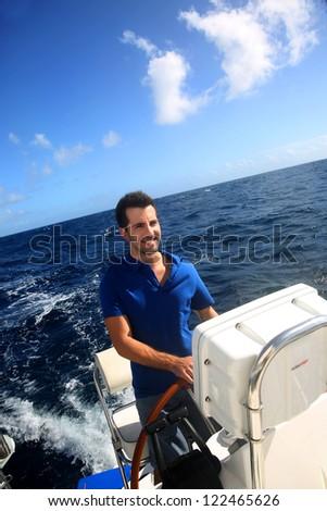 Smiling young sailor navigating in Caribbean sea - stock photo