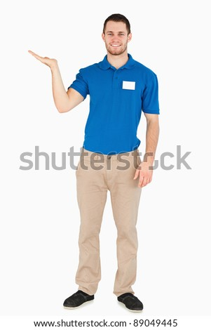 Smiling young salesman presenting in his palm against a white background - stock photo