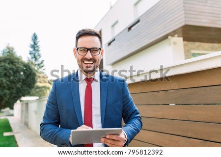 Smiling young salesman standing in front of the house