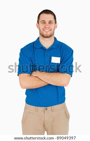 Smiling young salesman with folded arms against a white background - stock photo